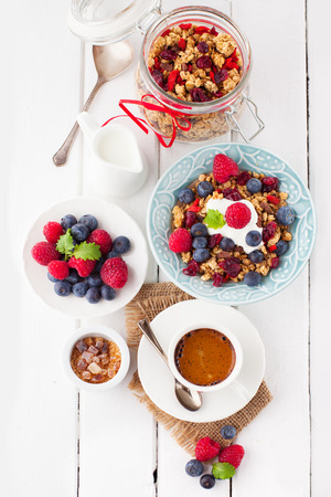 Healthy breakfast - cup of coffee, muesli and fresh berries on white wooden background, top view, health and diet concept photo