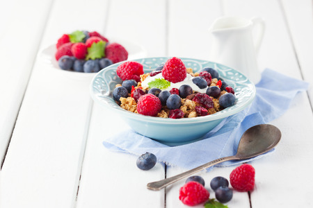 Healthy breakfast - muesli, milk and fresh berries on white wooden background, selective focus, health and diet concept photo