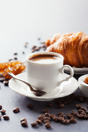 Crispy fresh croissants and cup of coffee espresso on a black background, morning breakfast, selective focus