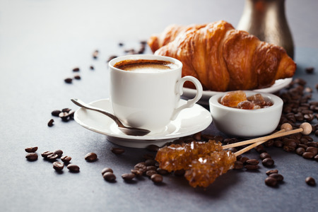 Crispy fresh croissants and cup of coffee on a black background, morning breakfast, selective focus 스톡 콘텐츠