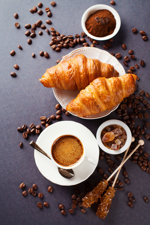 Crispy fresh croissants and cup of coffee on a black background, morning breakfast, selective focus Stockfoto