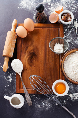 Ingredients and tools for baking - flour, eggs and rolling pin on the black background, top view
