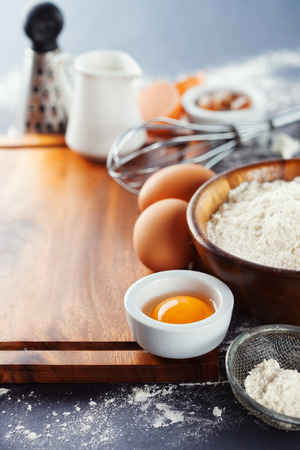 Ingredients and tools for baking - flour, eggs and rolling pin on the black background, selective focus