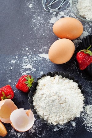 Ingredients and tools for baking - flour, eggs, rolling pin and fresh berries on the black background, top view