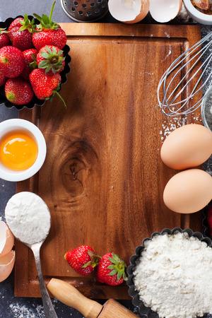 Ingredientes y herramientas para hornear - harina, huevos, rodillo y bayas frescas en el fondo negro, vista desde arriba Foto de archivo - 40450165