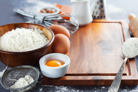 Ingredients and tools for baking - flour, eggs, sugar and rolling pin on the black background, selective focus photo