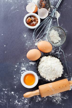 ustensiles de cuisine: Ingrédients et outils pour la cuisson - la farine, les oeufs et un rouleau à pâtisserie sur le fond noir, vue de dessus