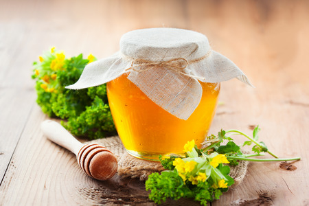 Full honey pot and honey stick with summer flowers on rustic wooden background, selective focus