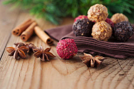 Assorted dark chocolate truffles with dried strawberry pieces and chopped hazelnuts on rustic wooden background, selective focus. 免版税图像