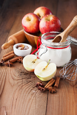 ingredients: Fresh red apples, spices and baking ingredients for apple pie on rustic wooden background, selective focus