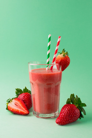 Fresh organic strawberry smoothie in a glass with ingredients on green background, selective focus Zdjęcie Seryjne