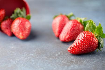 Juicy fresh strawberries on dark blue wooden background, selective focus