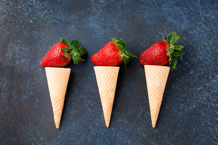 Fresh strawberries in waffle cones, healthy summer food concept, top view, dark blue background Zdjęcie Seryjne
