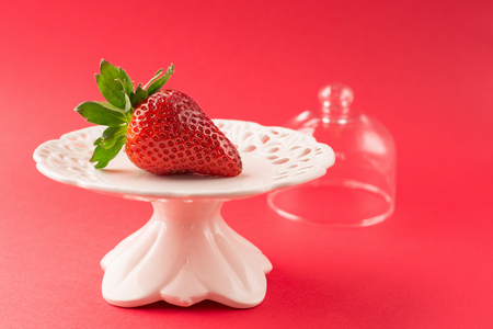 Juicy fresh strawberry on red background, selective focus