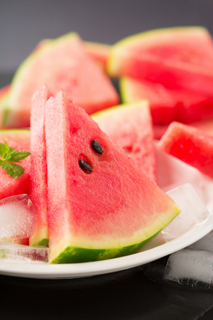 Fresh ripe watermelon slices and ice on black background, selective focus. Summer time concept