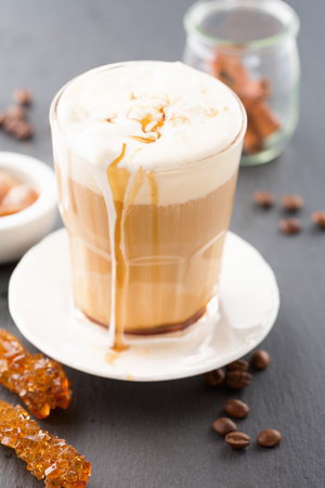Glass of caramel latte coffee with whipped cream and coffee beans on a black background, selective focus