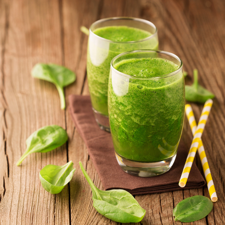 Fresh healthy green spinach smoothie with ingredients on rustic wooden background, selective focus