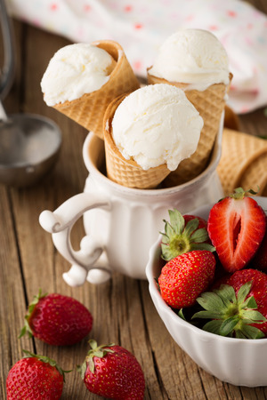 Vanilla ice cream in a waffle cones with fresh strawberries on rustic wooden background, selective focus