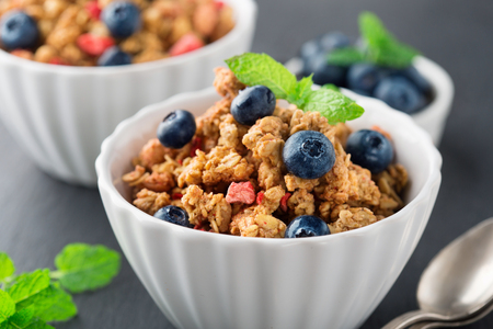 Healthy breakfast with homemade granola, milk, honey and fresh berries on black background, selective focus