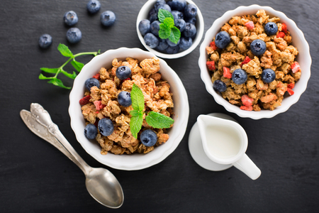 Healthy breakfast with granola, milk, honey and fresh berries on black background, top view