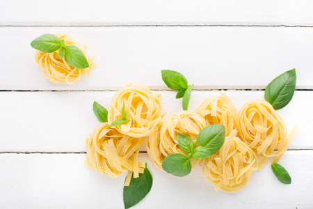 Italian traditional raw pasta and basil on white wooden background, top view