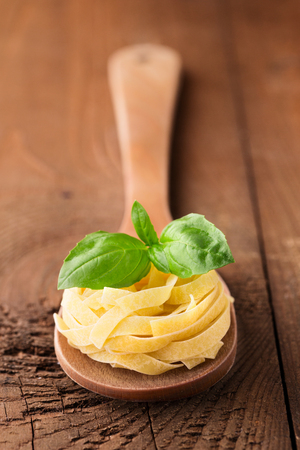 Italian traditional raw pasta and basil on rustic wooden background, selective focus