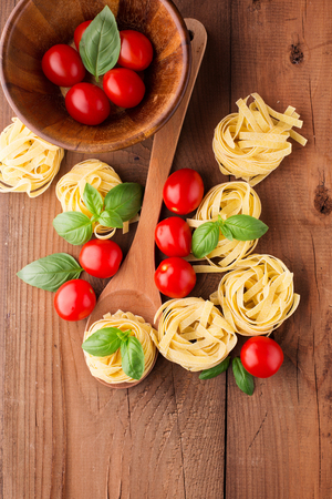 Ingredients for cooking pasta. Raw tagliatelle, basil and tomatoes on the rustic wooden background, top view