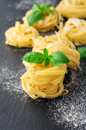 Italian traditional raw pasta and basil on the black stone background, selective focus
