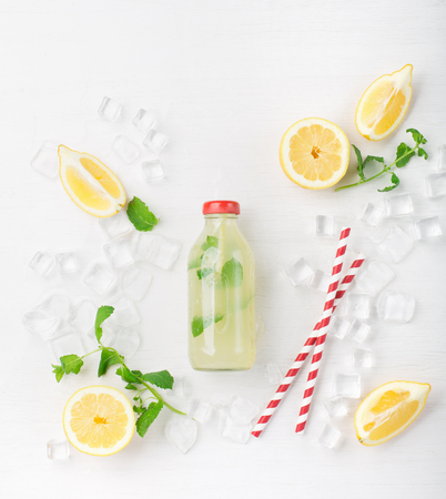 Fresh homemade summer  lemonade or mojito cocktail with lemon and mint. Cold refreshing drink or beverage with ice on white background, top view Zdjęcie Seryjne