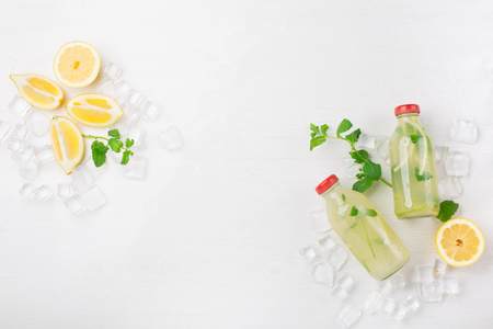 Fresh homemade summer  lemonade or mojito cocktail with lemon and mint. Cold refreshing drink or beverage with ice on white background, top view Foto de archivo - 125482999