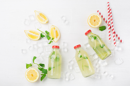 Fresh homemade summer  lemonade or mojito cocktail with lemon and mint. Cold refreshing drink or beverage with ice on white background, top view Foto de archivo - 125483001