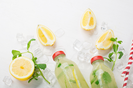 Fresh homemade summer  lemonade or mojito cocktail with lemon and mint. Cold refreshing drink or beverage with ice on white background, selective focus