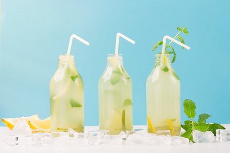 Fresh homemade summer  lemonade or mojito cocktail with lemon and mint. Cold refreshing drink or beverage with ice on white and blue background Zdjęcie Seryjne