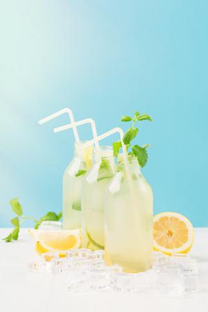 Verse zelfgemaakte zomerlimonade of mojitococktail met citroen en munt. Koude verfrissende drank of drank met ijs op witte en blauwe achtergrond