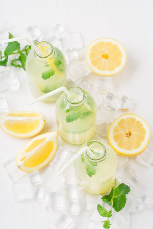Fresh homemade summer  lemonade or mojito cocktail with lemon and mint. Cold refreshing drink or beverage with ice on white background, selective focus Foto de archivo - 125483014