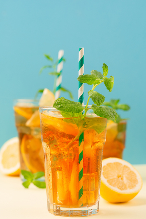 Traditional iced tea with lemon, mint and ice in tall glasses. Summer cold drink on blue background