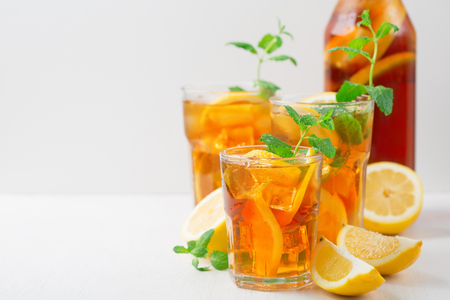 Traditional iced tea with lemon, mint and ice in tall glasses. Summer cold drink on white background Zdjęcie Seryjne