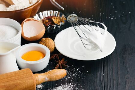 Baking ingredients for homemade pastry on dark rustic wooden background. Bake sweet cake dessert concept. Selective focus