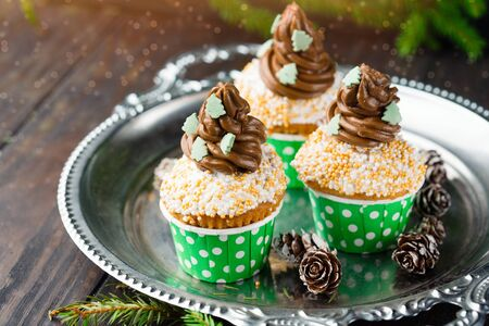 Christmas vanilla Cupcakes with chocolate buttercream icing and holiday decorations on the rustic wooden table, selective focus. Winter time concept Stok Fotoğraf