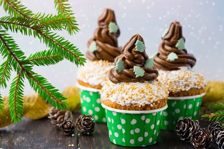 Christmas vanilla Cupcakes with chocolate buttercream icing and holiday decorations on rustic wooden table, selective focus. Holiday time concept