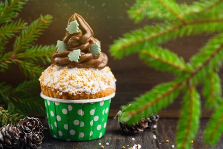 Christmas vanilla Cupcakes with chocolate buttercream icing and holiday decorations on the rustic wooden table, selective focus Stok Fotoğraf