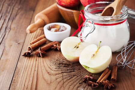 Fresh red apples, spices and baking ingredients for apple pie on rustic wooden background, selective focus. Autumn thanksgiving day consept Stok Fotoğraf