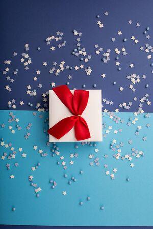 선물, 작은 별, 흰색 선물이 있는 해피 발렌타인 데이 카드에는 고전적인 파란색 배경에 빨간 활이 있습니다. 휴일 시간 개념입니다. 모형 템플릿입니다. 평면도 스톡 콘텐츠