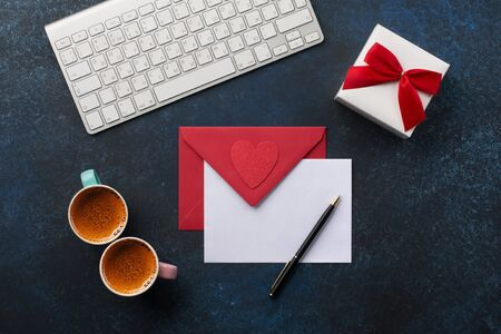 Empty card with Red envelope on classic blue background. Love letter, Valentines card, holiday time concept. Gift and two cups of coffee on office desk. Banco de Imagens