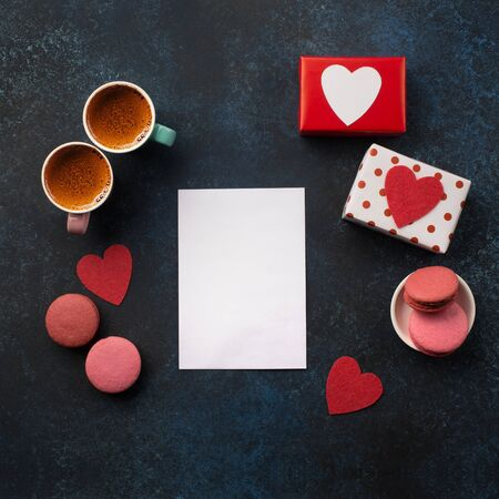 White paper card on classic blue background. Love letter, Valentines card, holiday letter, gift, macaroons and two cups of coffee. Holiday time concept