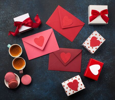 Red envelopes, gifts, two cups of coffee and macaroons on classic blue background . Love letter, Valentines card, holiday time concept. Mockup template. Top view