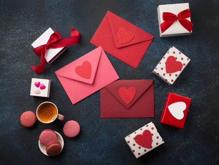 Red envelopes, gifts, cup of coffee and macaroons on classic blue background . Love letter, Valentines card, holiday time concept. Mockup template. Top view Banco de Imagens