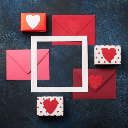 Red envelopes, gifts and red hearts on classic blue background. Love letter, Valentines card, holiday time concept. Mockup template. Top view Banco de Imagens