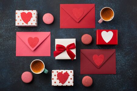 Red envelopes, gifts, cup of coffee and macaroons on classic blue background. Love letter, Valentines card, holiday time concept. Mockup template. Top view Banco de Imagens
