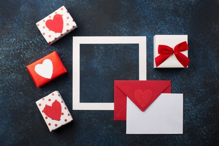 Valentines day, birthday, wedding or other holiday composition. Empty card with Red envelope, gifts and hearts. Mockup template. View from above